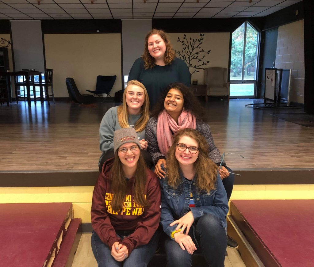 Five students smiling and sitting on the Wesley at CMU stage.